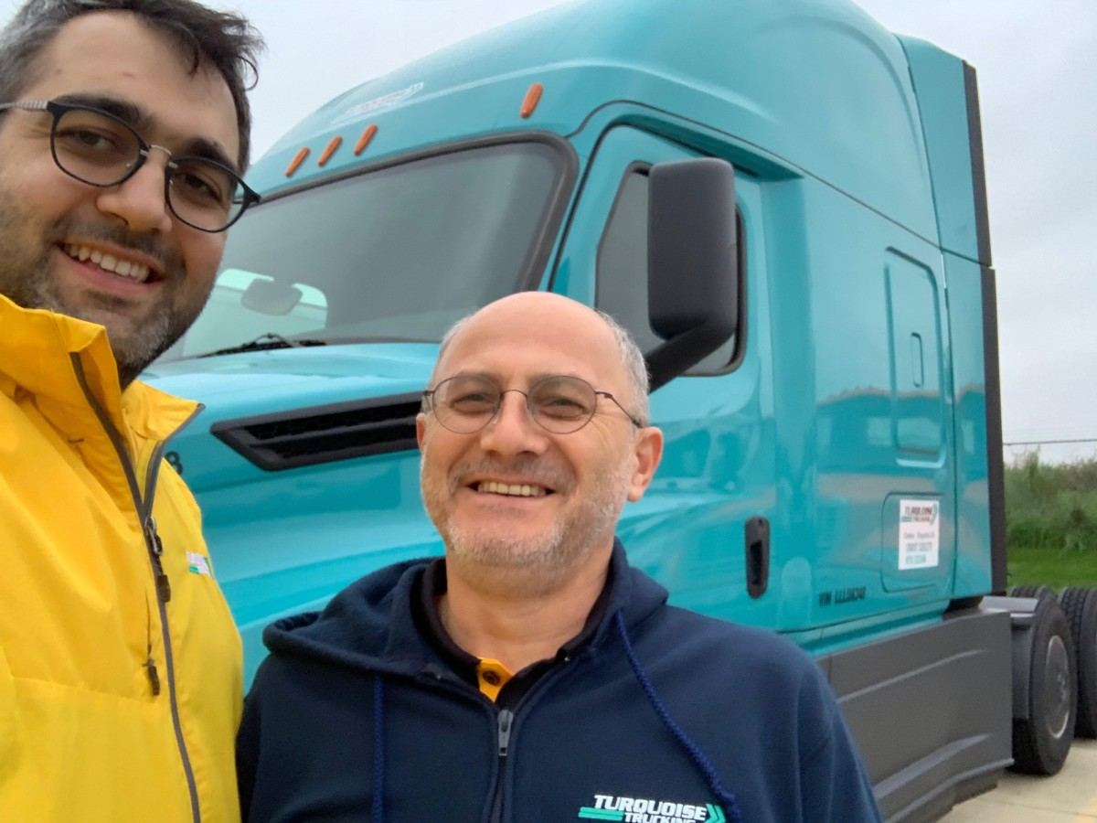 Photo of two smiling men in front of a Turquoise truck.